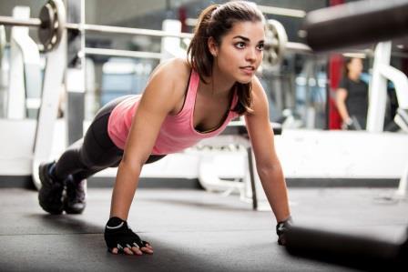 Занятие спортом в спортзале - девушка во время тренировки